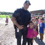 Officer Thomas Oare meets with a student on the playground at the elementary school