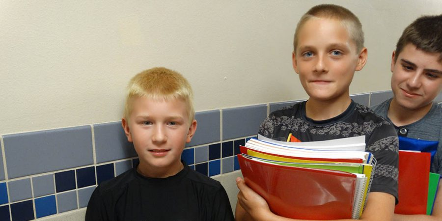Students wait in the hallway with books in their hands