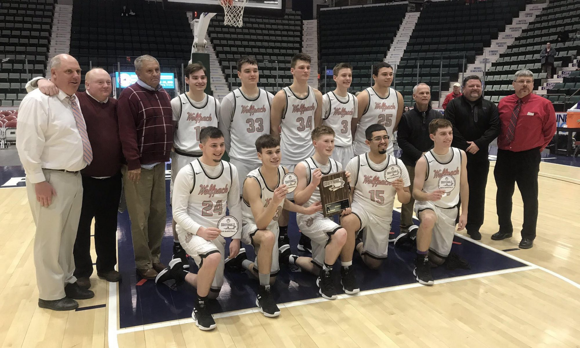 Boys Basketball team posing with Sectional Championship plaque.
