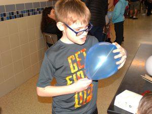 Student pressing a skewer through a balloon