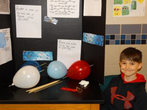 Student showing off a science display