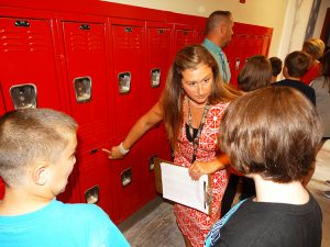 Teacher showing students how to use lockers